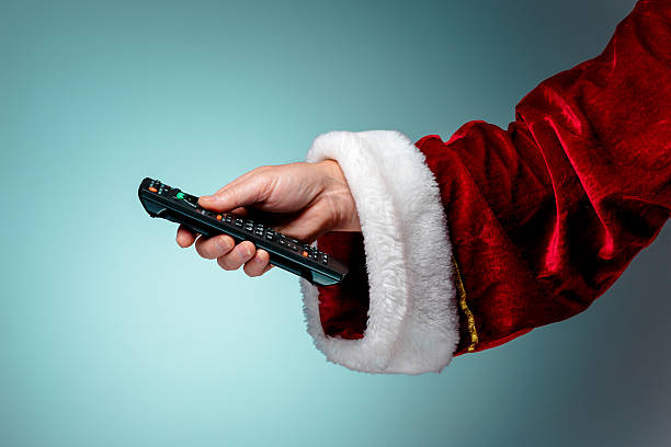 santa claus holding tv remote control - christmas movie foto e immagini stock
