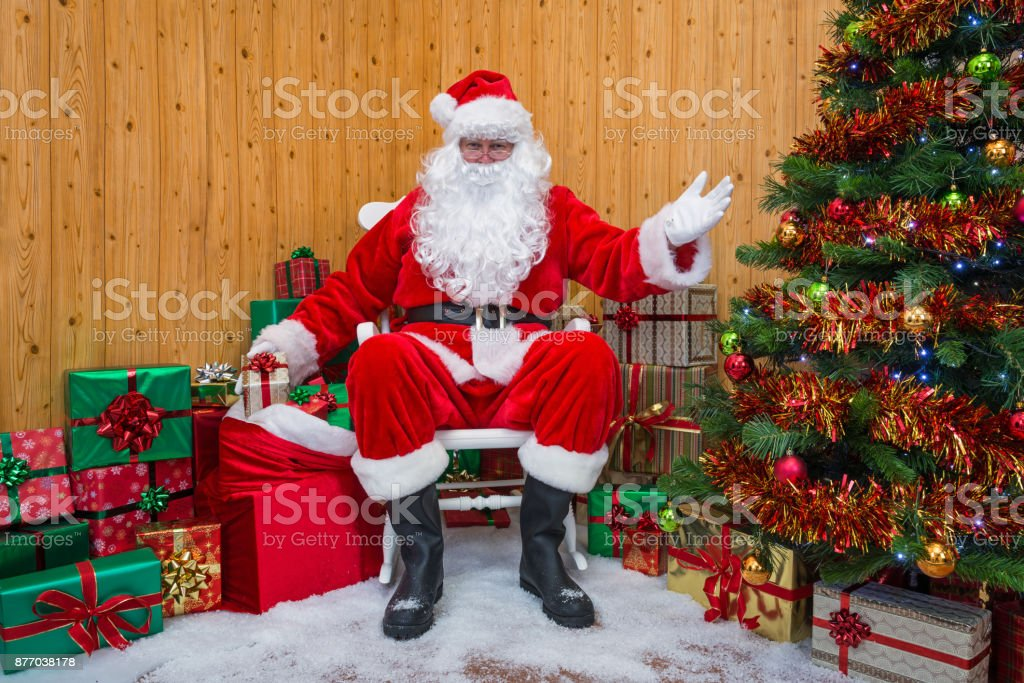 Santa Claus in a grotto handing out presents. stock photo