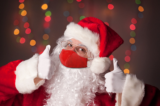Santa Claus in his coronavirus face mask with two thumbs up for approval.