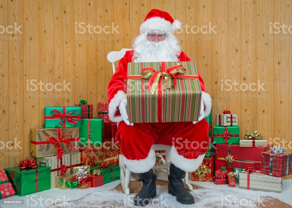 Santa Claus in his grotto holding a gift wrapped present stock photo