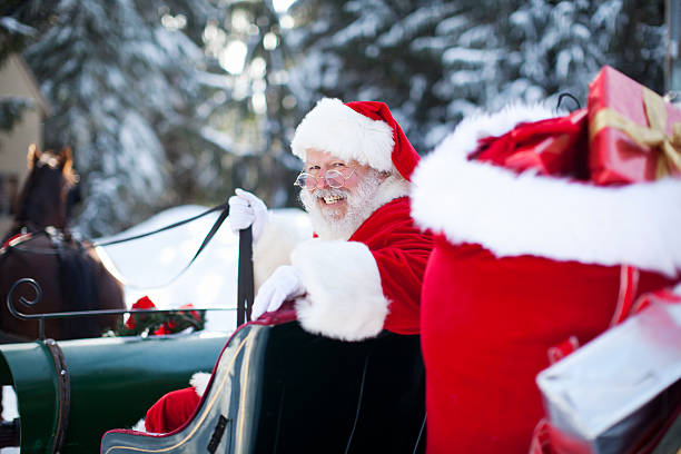 Santa Claus in His Sleigh at North Pole Santa Claus in his horse driven sleigh with presents at the North Pole, surrounded by snow. Copy space. sleigh stock pictures, royalty-free photos & images