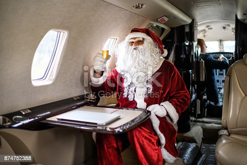 istock Santa Claus in private jet airplane 874752388