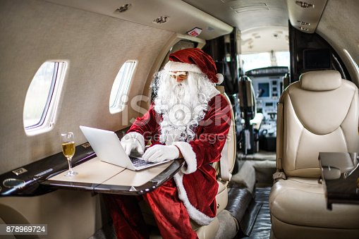 istock Santa Claus in private jet airplane 878969724