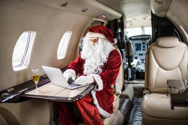 santa claus im privat-jet flugzeug - weihnachtsprogramm stock-fotos und bilder
