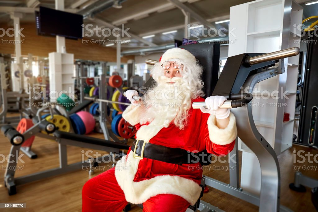 Santa Claus in the gym doing the exercises stock photo