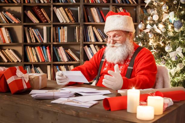 weihnachtsmann in der bibliothek weihnachts-neujahrskonzept - santa stock-fotos und bilder