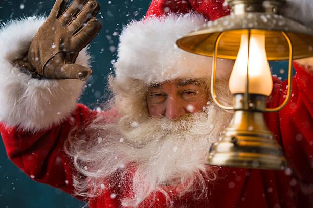 babbo natale sta con un fulgido lanterna - santa claus tiptoeing foto e immagini stock