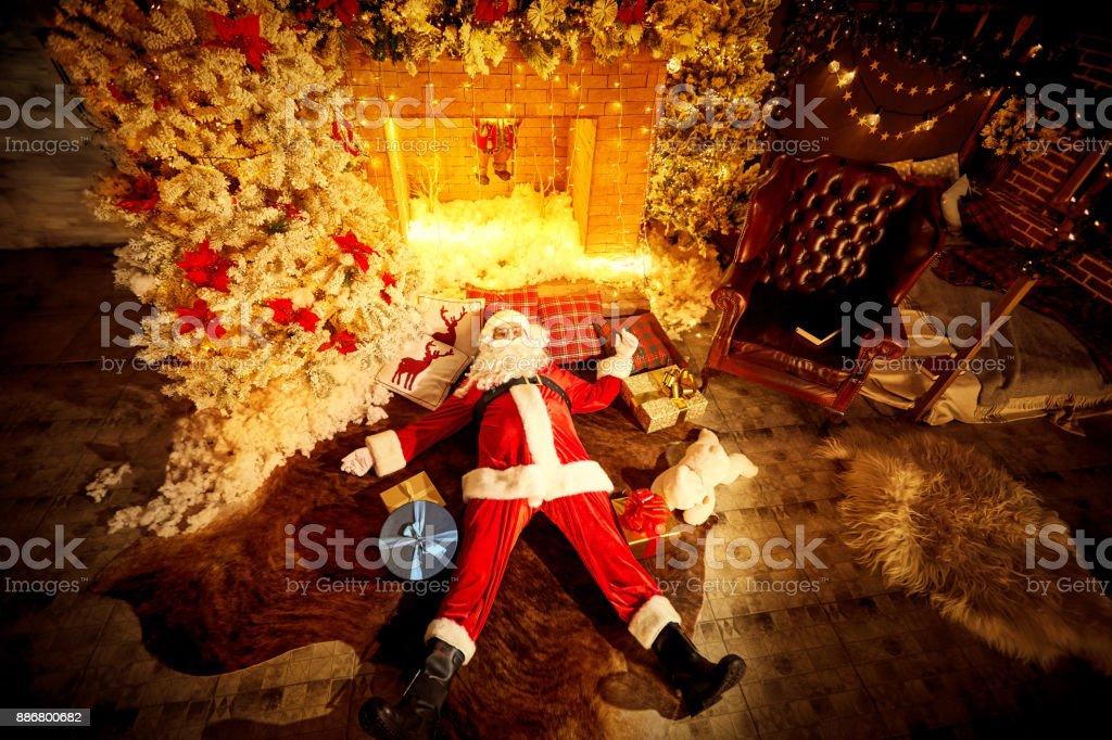 Santa Claus est allongé ivre sur le sol devant la cheminée après C - Photo