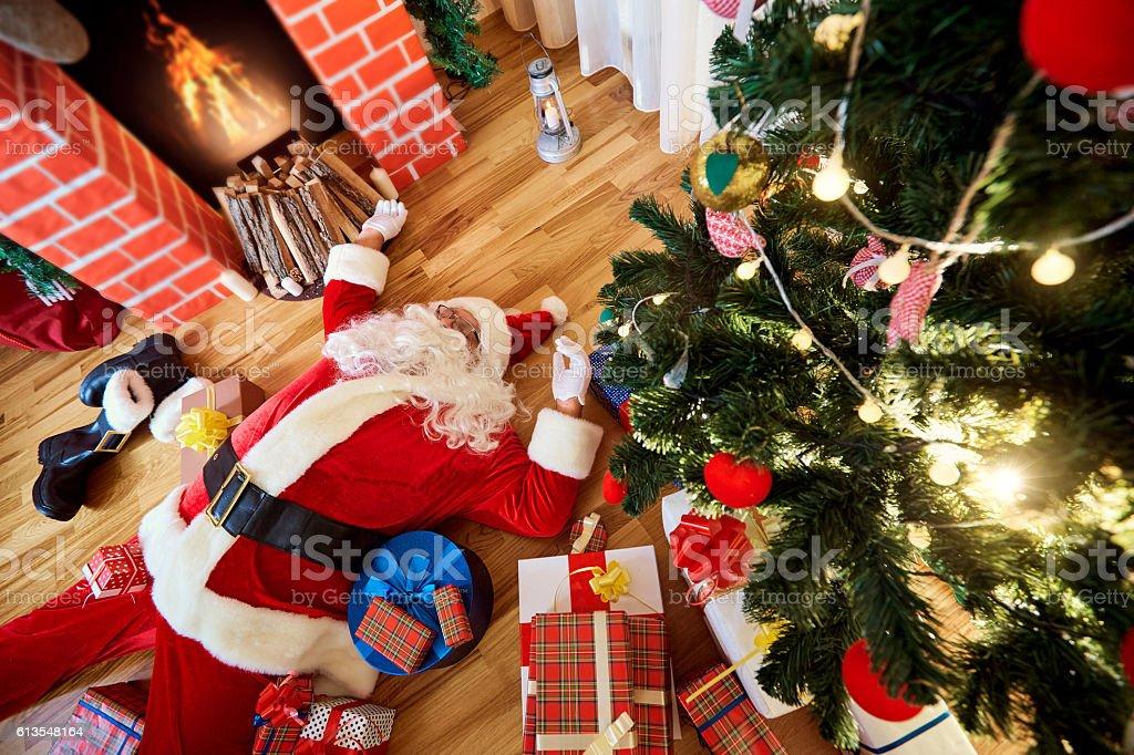 Santa Claus is sleeping, tired, drunk in  room near  firepla stock photo