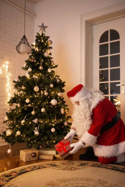 weihnachtsmann ein geschenk unter dem weihnachtsbaum am heiligen abend verlassen - abschiedswünsche stock-fotos und bilder