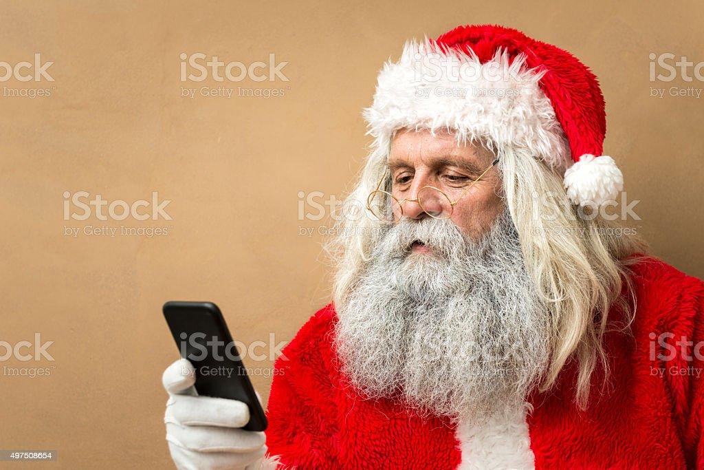 santa claus looking at smart phone stock photo