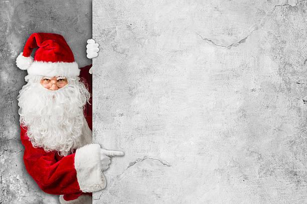 santa claus looking behind empty concrete billboard sign wall - gutschein weihnachten stock-fotos und bilder