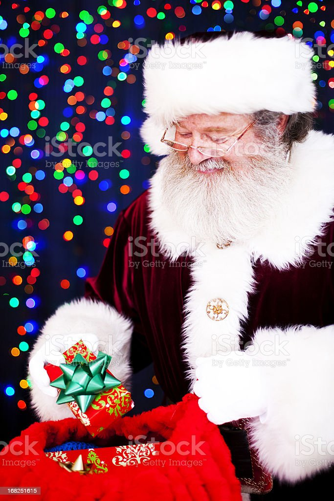Santa Claus Looking in Sack of Presents stock photo