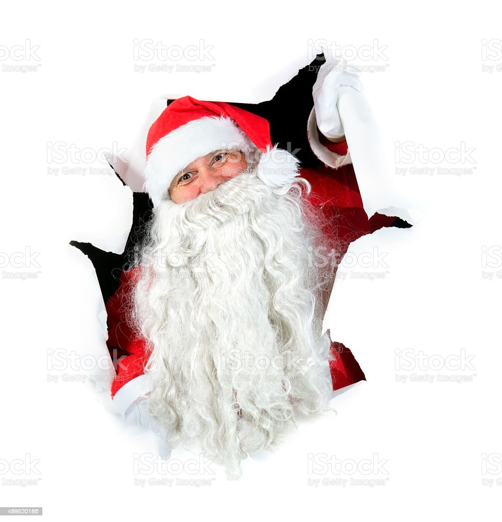 Santa Claus looking out of a hole stock photo