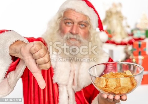 Santa Claus make thumbs down sign to the unhealthy eating and potato chips, focus on hand. The scene is located in a studio environment within prepared Christmas set with tree, presents, angels, lights, balls and other christmassy decoration. The footage is taken with Sony A7III camera.