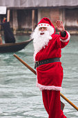 """""""Venice, Italy - February 19, 2012: Santa Claus mask participant of the 2012 carnival celebrations greeting casual photographers and tourists on a gondola over Gran Canal"""""""