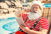 Santa Claus near the pool holiday concept using digital tablet