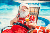 Santa Claus near the pool holiday concept drinking juice
