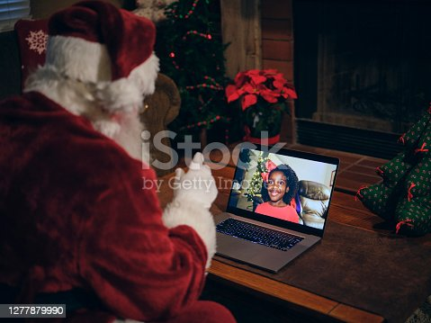 Santa Claus using a computer in his house to do a Christmas videoconference with a child.