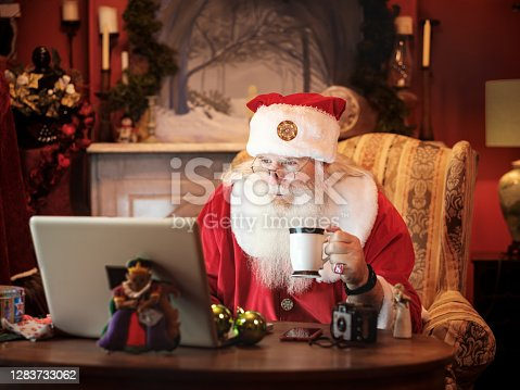 Santa Claus using a computer in his house to do a Christmas video conference. He is holding a cup with hot drink.