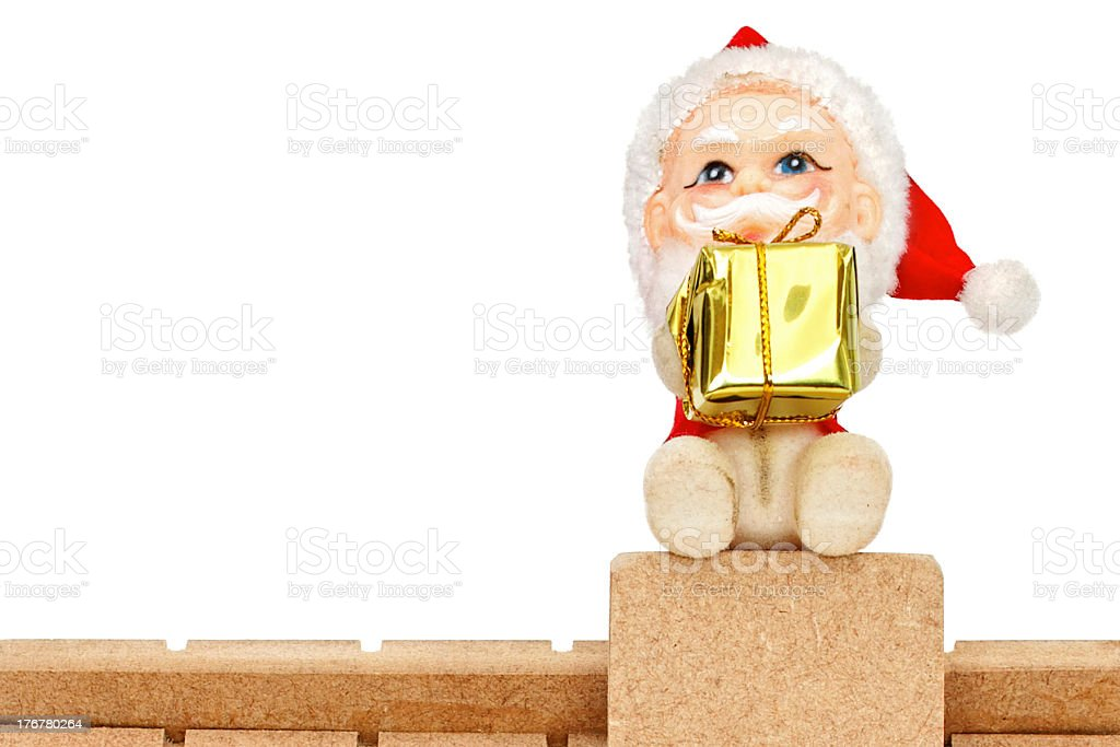 Santa Claus on roof holding a gift royalty-free stock photo