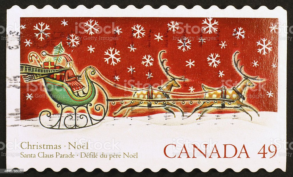 Santa Claus on sleigh pulled by reindeers, stamp stock photo