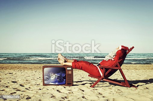 Santa Claus on the beach, relaxing and sunbathing with feet resting on a vintage TV.