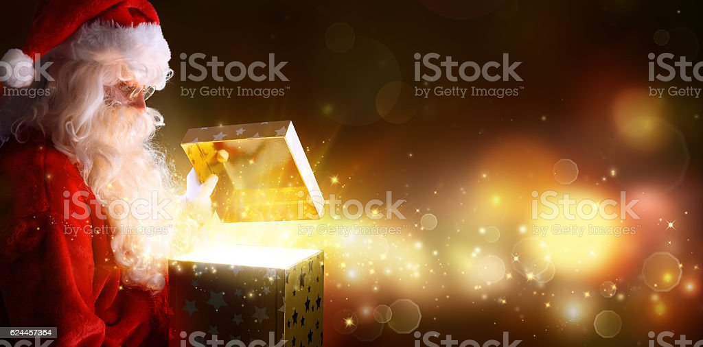 Santa Claus Opening Christmas Present With Shiny Stars - foto stock