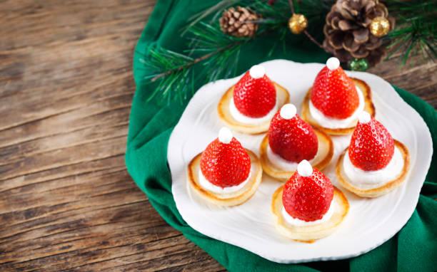 weihnachtsmann pfannkuchen mit schlagsahne und erdbeeren, weihnachts-food-idee - weihnachtsmannhüte aus erdbeeren stock-fotos und bilder
