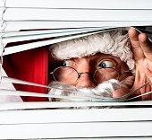 Santa Claus peeking through the blinds on a window