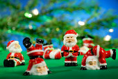 Santa Claus figures in front of the branch of a Christmas tree