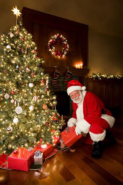 decorate albero di natale e babbo natale con regali - santa claus tiptoeing foto e immagini stock