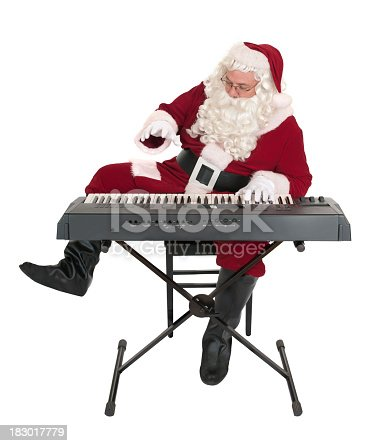 Santa Claus wildly playing a synthesizer keyboard.   Isolated on white.