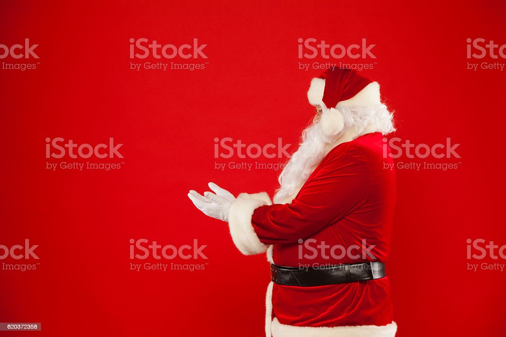 Santa Claus pointing in blank a place, red background foto de stock royalty-free