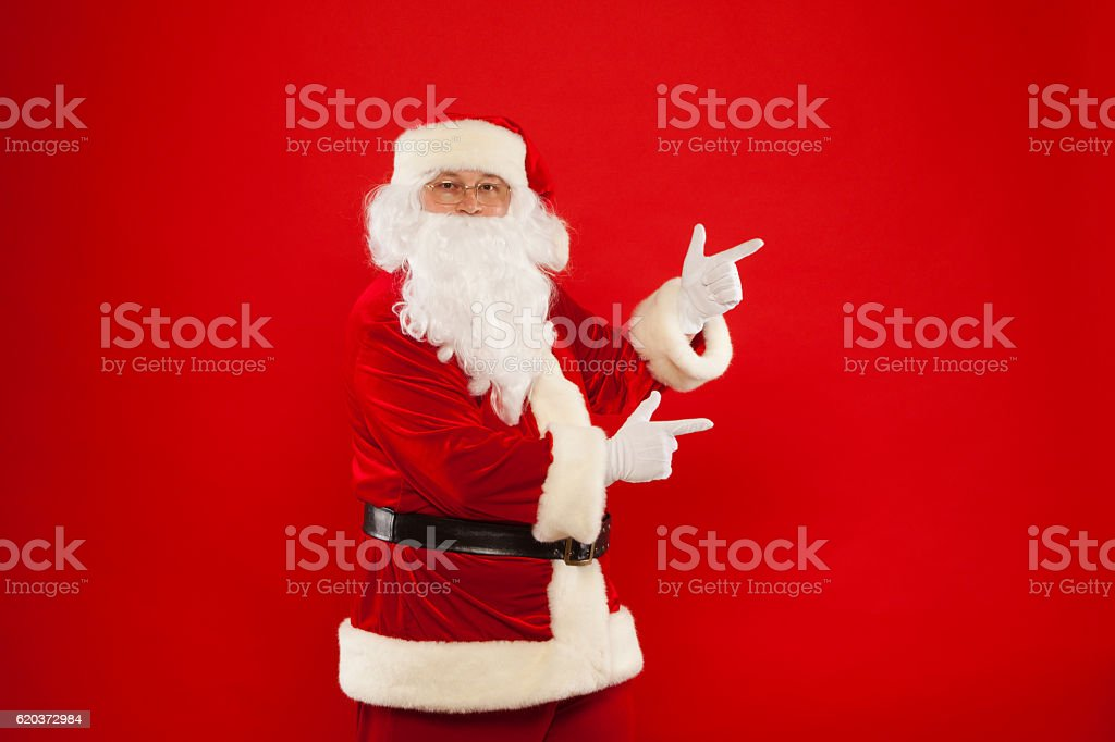 Santa Claus pointing in blank a place, red background zbiór zdjęć royalty-free