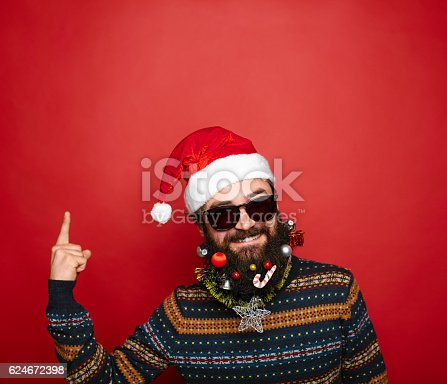 istock Santa Claus pointing in blank red banner, isolated on white 624672398
