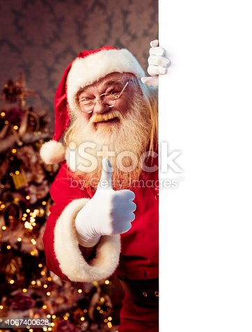 1069359694 istock photo Santa Claus pointing on blank banner 1067400628