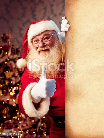 istock Santa Claus pointing on blank banner 1073122366