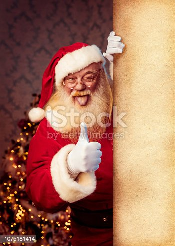 1069359694 istock photo Santa Claus pointing on blank banner 1075181414