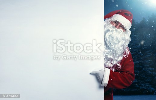 istock Santa Claus pointing on blank banner 625740902