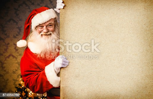 1069359694 istock photo Santa Claus pointing on blank banner 874554286