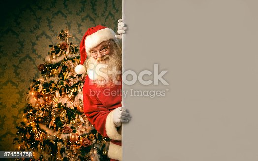 1069359694 istock photo Santa Claus pointing on blank banner 874554758