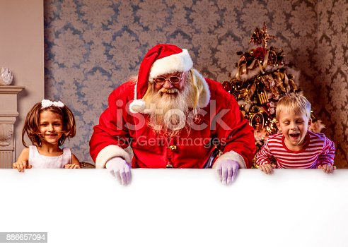 1069359694 istock photo Santa Claus pointing on blank banner 886657094