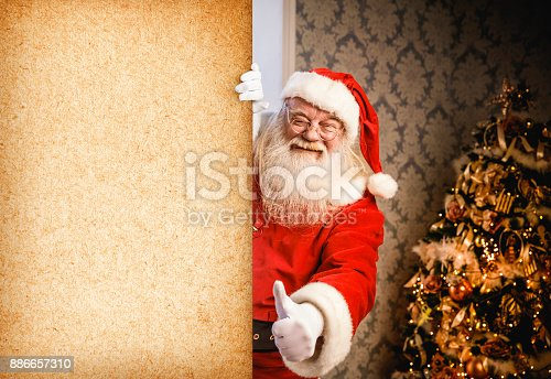 1069359694 istock photo Santa Claus pointing on blank banner 886657310