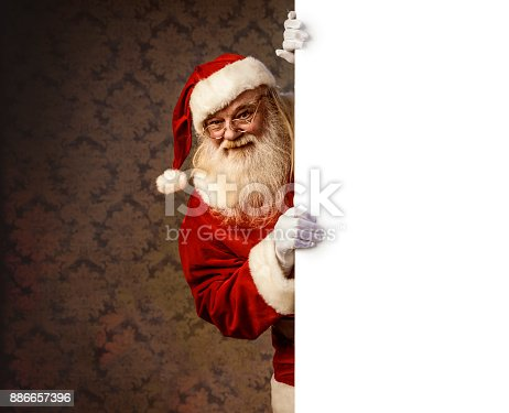 istock Santa Claus pointing on blank banner 886657396