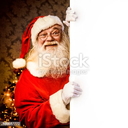 istock Santa Claus pointing on blank banner 886657772