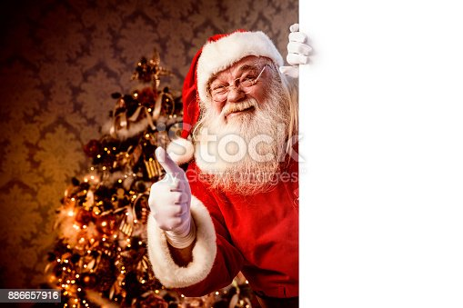 istock Santa Claus pointing on blank banner 886657916