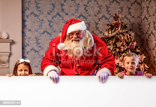 istock Santa Claus pointing on blank banner 886658144