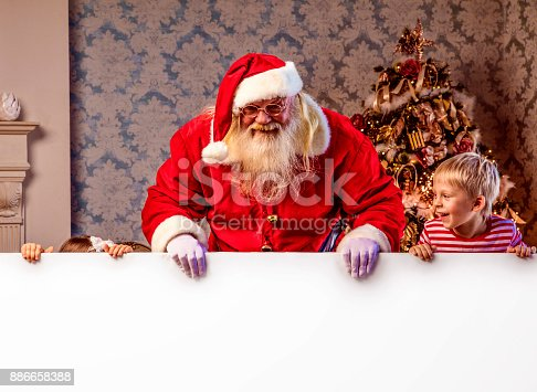 istock Santa Claus pointing on blank banner 886658388