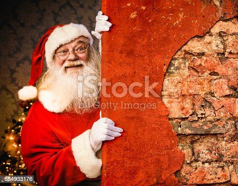 istock Santa Claus pointing on brick wall 884933176